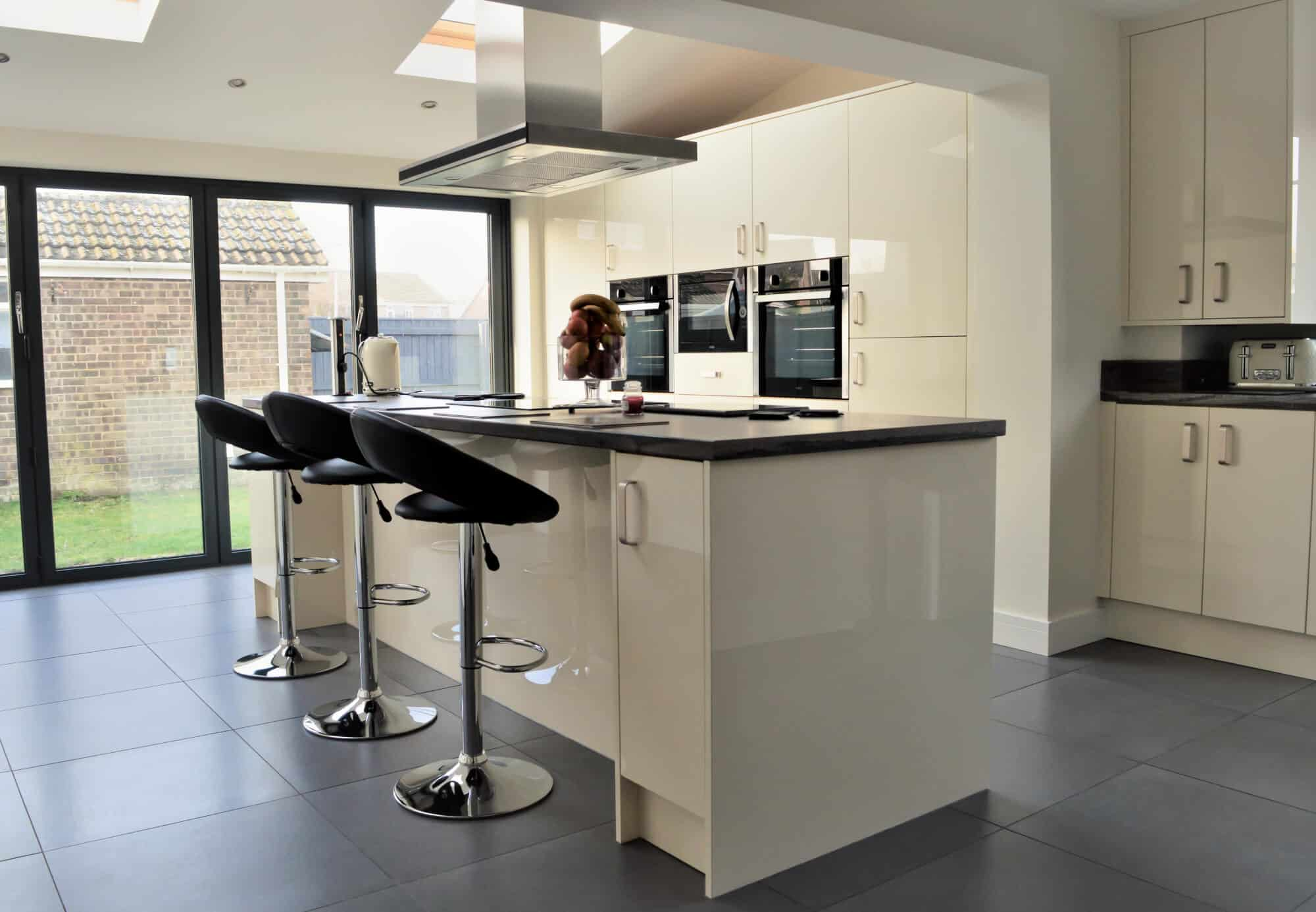 Contemporary kitchen with laminated door and drawer fronts and breakfast bar